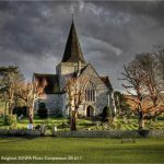 Divine Light by James Ringland, shortlisted for SDNPA Photo Competition 2016/17. Bright sun catches on bare lime tree branches, highlighting bright new stems and picking out the flint-walled detail of St Andrew's Church in defiance of the petrol skies. The storm clouds may be on their way but for now the Cathedral of the South Downs bathes in light.